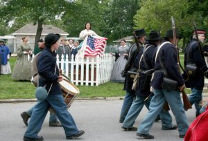 Alyssa Gonzales is dressed as Lucy Hood in Civil War era clothing. She's taken off a petticoat with an American flag, waving it to Union soldiers as they march by.