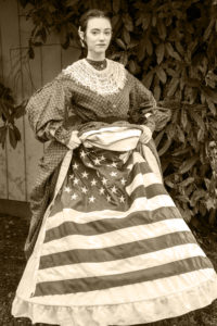 Danielle Yrulegui dressed in an 1860's Civil War day dress with a hoopskirt and petticoats. She's lifted her dress and petticoats to show a Union flag beneath, looking at the camera. The picture is sepia-toned.