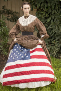 Danielle Yrulegui dressed in an 1860's Civil War day dress with a hoopskirt and petticoats. She's lifted her dress and petticoats to show a Union flag beneath, looking towards someone out of frame..
