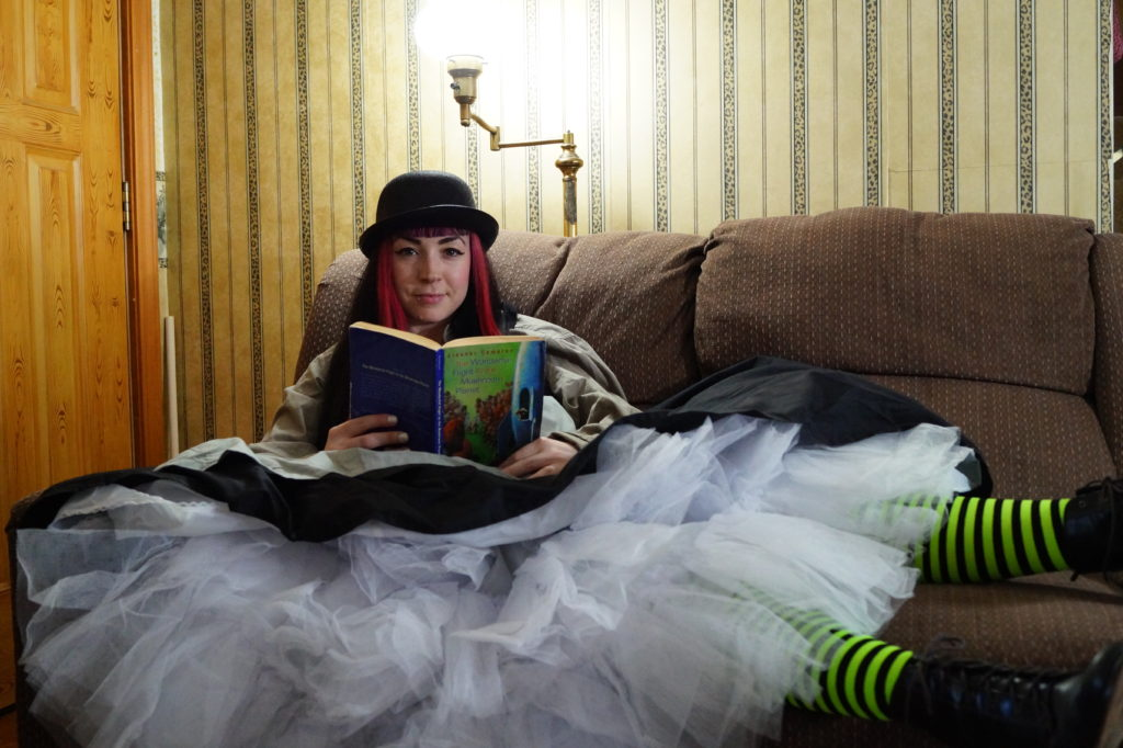 A steampunk woman in pink hair and a bowler hat on a couch, skirts spread out all over the place and showing crinoline tulle, along with neon green striped stocking. She's reading the book The Wonderful Flight to the Mushroom Planet, while looking at the viewer